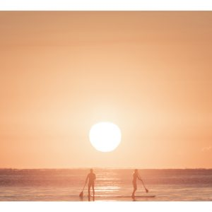 Travelling Light - photograph of paddle boarders in the surf at Mudjimba
